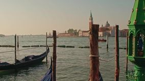 Gôndola estacionadas na praça San Marco e na terraplenagem do palácio do doge com a torre de sino de Saint Giorgio Maggiore filme