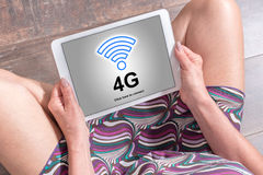 4g network concept on a tablet. Woman sitting on the floor with a tablet showing 4g network concept Royalty Free Stock Photo
