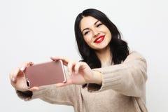 G?r den curvy brunettflickan f?r mode som tar fotoet, sj?lvst?enden p? smartphonen royaltyfria bilder
