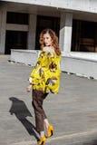 G?r ikl?dd guling f?r den slanka stilfulla brunettflickan med den bruna blommablusen i gatan p? en solig dag royaltyfria foton