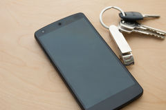4G Smartphone wite house key on wood floor.  Royalty Free Stock Image