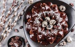 G?teau de P?ques avec du chocolat, noix de coco, fleurs de ressort, oeufs de caille sur un fond en pierre C?l?bration heureuse de photo stock