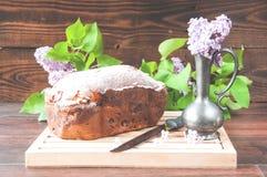 G?teau fait maison cuit au four ?pousset? avec des supports de poudre d'un plat blanc pr?s des fleurs lilas photographie stock