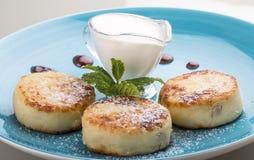 G?teaux au fromage de petit d?jeuner avec la cr?me sure d'un plat bleu photos libres de droits