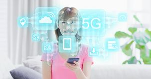 5G technology concept. Young woman hold smart phone and see 5G technology virtual screen interface stock photography