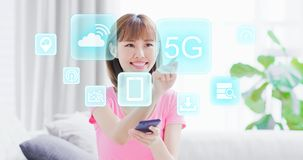 5G technology concept. Young woman hold smart phone and touch 5G technology icon with virtual screen interface stock photos
