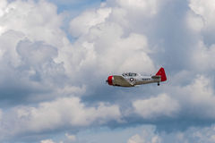AT-6G Texan Flies By Clouds. EDEN PRAIRIE, MN - JULY 16, 2016: AT-6G Texan airplane flies by through cloudy sky at air show. The AT-6 Texan was primarily used as Royalty Free Stock Images