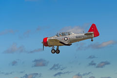 AT-6G Texan Flies By Ragged Clouds Stock Photo