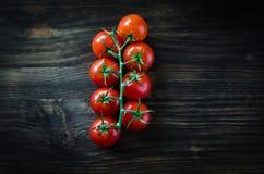 Gałąź czerwoni organicznie czereśniowi pomidory na drewnianym tle Obrazy Royalty Free