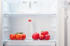 Gałąź czerwoni pomidory, dwa czerwonego pieprzu, dwa dwubarwnej brzoskwini i butelka woda na półce otwarty pusty refri, pomarańcz Obraz Stock