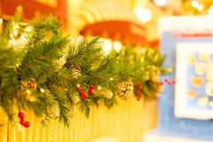 Gałęziaści bożych narodzeń bordry dekorujący z jagodami holly i rożki na kolor żółty powierzchni tle z kopią interliniują boże na Fotografia Royalty Free