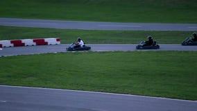 Ga -gaan-kart raceauto's die voor de eerste plaats op het concrete spoor concurreren stock videobeelden