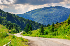 Gaat de Horisontal windende weg naar bergen onder een bewolkte hemel Stock Afbeelding