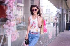 Gaat de manier mooie vrouw rond de stad in glazen en pakketten Stock Foto