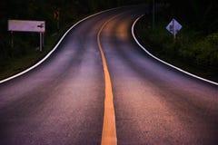 Gaat de ochtend windende weg met gele lijn in donker bos Stock Fotografie