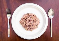 Gaba rice in a dish made of recycled materials on a wooden table with cutlery placed.  stock photography