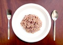Gaba rice in a dish made of recycled materials on a wooden table with cutlery placed.  stock images