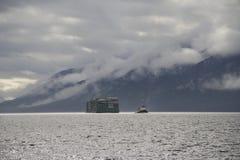 Gabarra remolcada por el remolcador en las nubes costeras de Alaska y el fondo montañoso Fotografía de archivo