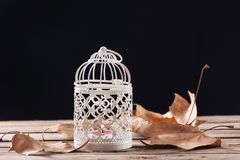 Gabbia decorativa con la combustione della candela sul retro scrittorio di legno immagini stock libere da diritti