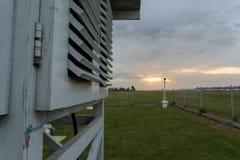Gabbia meteorologica sotto il cielo nuvoloso grigio fotografie stock
