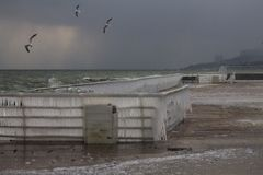 Gabbiani sopra il mare tempestoso vicino ad una banchina Fotografia Stock Libera da Diritti