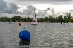 Gabbiano che si siede su una boa blu sul lago fotografia stock