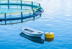 Gabbie per la piscicoltura e la barca Fotografie Stock