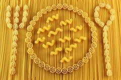 Gabel, Löffel und Platte hergestellt von den Spaghettis und von den Teigwaren lizenzfreie stockbilder