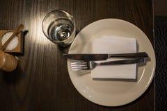 Gabel, Messer, Platte, Serviette und Glas dienten für Restaurant stockbild