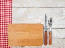 Gabel, Messer und hölzerne Platte Stockbilder