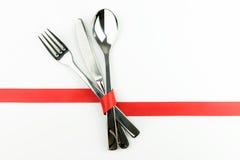 Gabel, Messer und Löffel oben gebunden mit rotem Band Stockfotos