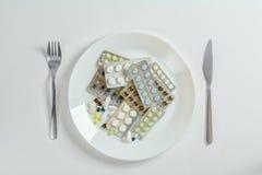 Gabel, Messer und weiße Platte mit Tabletten von verschiedenen Formen, von Größen und von Farben, Draufsicht Lizenzfreie Stockbilder