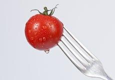Gabel mit einer kleinen Tomate Stockfotos