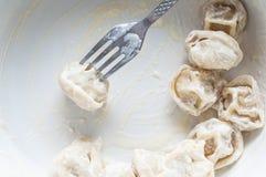 Gabel mit Schweinefleischmehlklößen in den appetitanregenden Blicken der Sahnesoße in einer weißen Platte mit halb fertigem stockfotografie