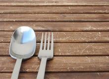 Gabel und Löffel auf einem Holztisch mit silbernen blauen Türkisreflexionen stockfotos