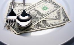 Gabel und Löffel auf Geld Stockfotografie