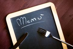 Gabel und Messer auf leerem Menü auf Tafel Lizenzfreies Stockfoto