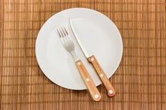 Gabel und Messer auf leerem Teller auf Bambustabellenmatte stockfotografie
