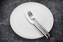 Gabel und Messer auf weißer Platte Stockbilder