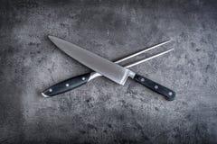 Gabel und Messer Gabel und Messer gekreuzt auf konkretem Brett Lizenzfreies Stockfoto
