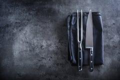 Gabel und Messer Schwarze Serviettentischdecke der Gabel und des Messers auf concre Lizenzfreies Stockfoto