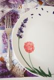 Gabel und Platte auf einer Serviette mit purpurroten Blumen stockfoto