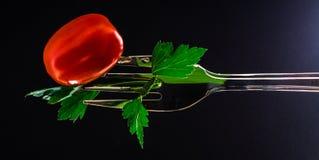 Gabeln Sie mit Tomate und Petersilie auf einem schwarzen Hintergrund lizenzfreie stockfotos