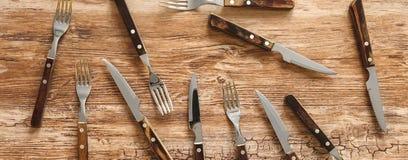 Gabeln und Messerfleischtischbesteck auf rustikalem Holztisch lizenzfreie stockfotografie