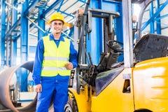 Gabelstaplerfahrer, der in der Produktionsanlage steht lizenzfreies stockfoto