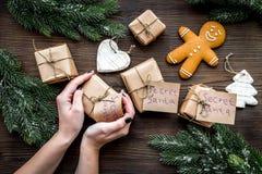 Gabentausch Hände halten Kasten mit Anmerkung Santa Secret nahe Fichtenzweig- und Lebkuchenplätzchen auf dunklem hölzernem stockfotografie