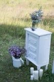 Gabinete blanco con las flores púrpuras el casarse en el estilo de prueba Imágenes de archivo libres de regalías
