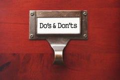 Gabinete de fichero de madera de la oficina con DOS y Donts Labe Imagenes de archivo