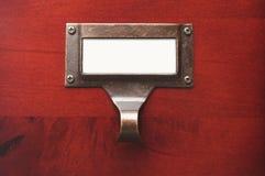 Gabinete de madeira brilhante com etiqueta de arquivo em branco Fotos de Stock Royalty Free