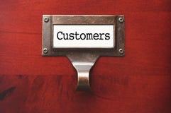 Gabinete de madera brillante con la etiqueta de fichero de clientes Imagenes de archivo
